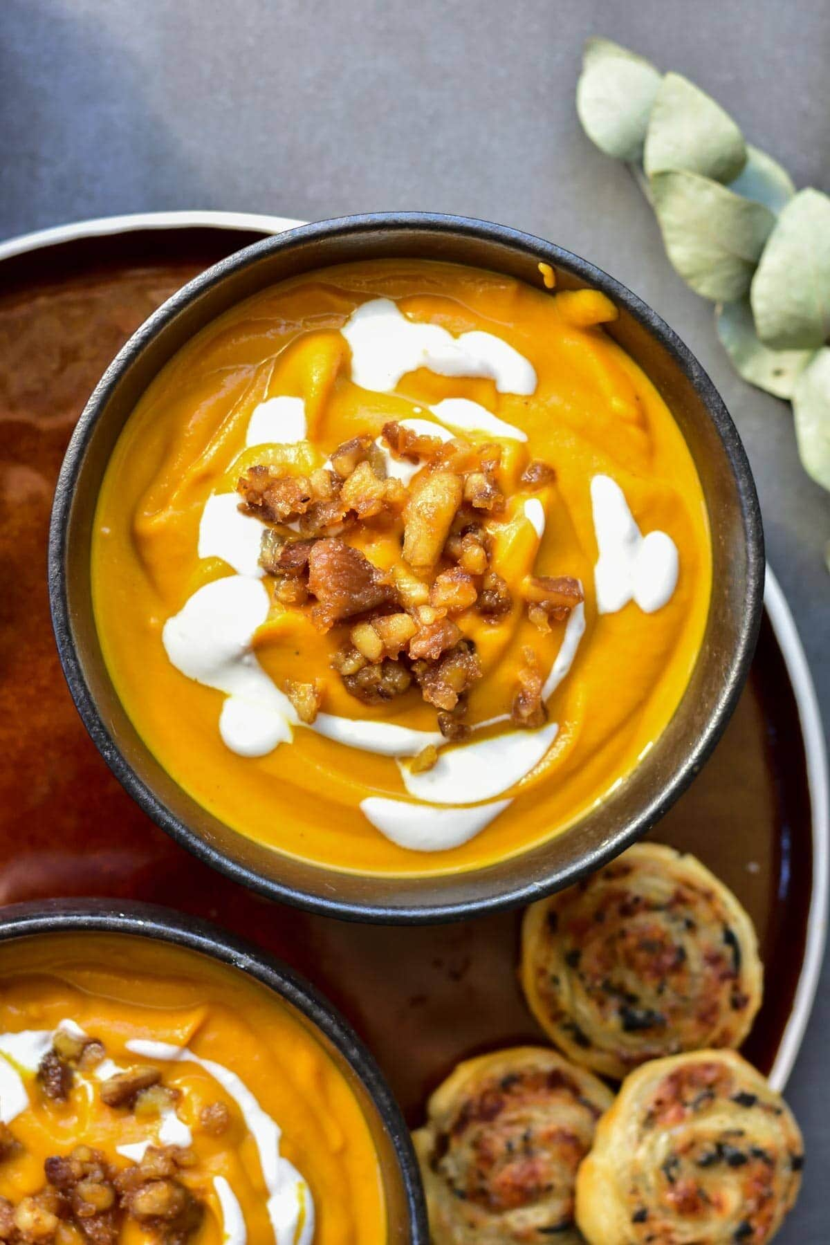 Pumpkin chestnut soup in a black bowl topped with caramelized chestnuts and yogurt.