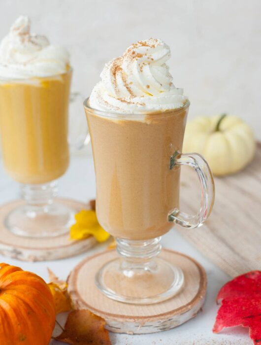 Two glasses with pumpkin spice hot chocolate topped with whipped cream and cinnamon sugar.