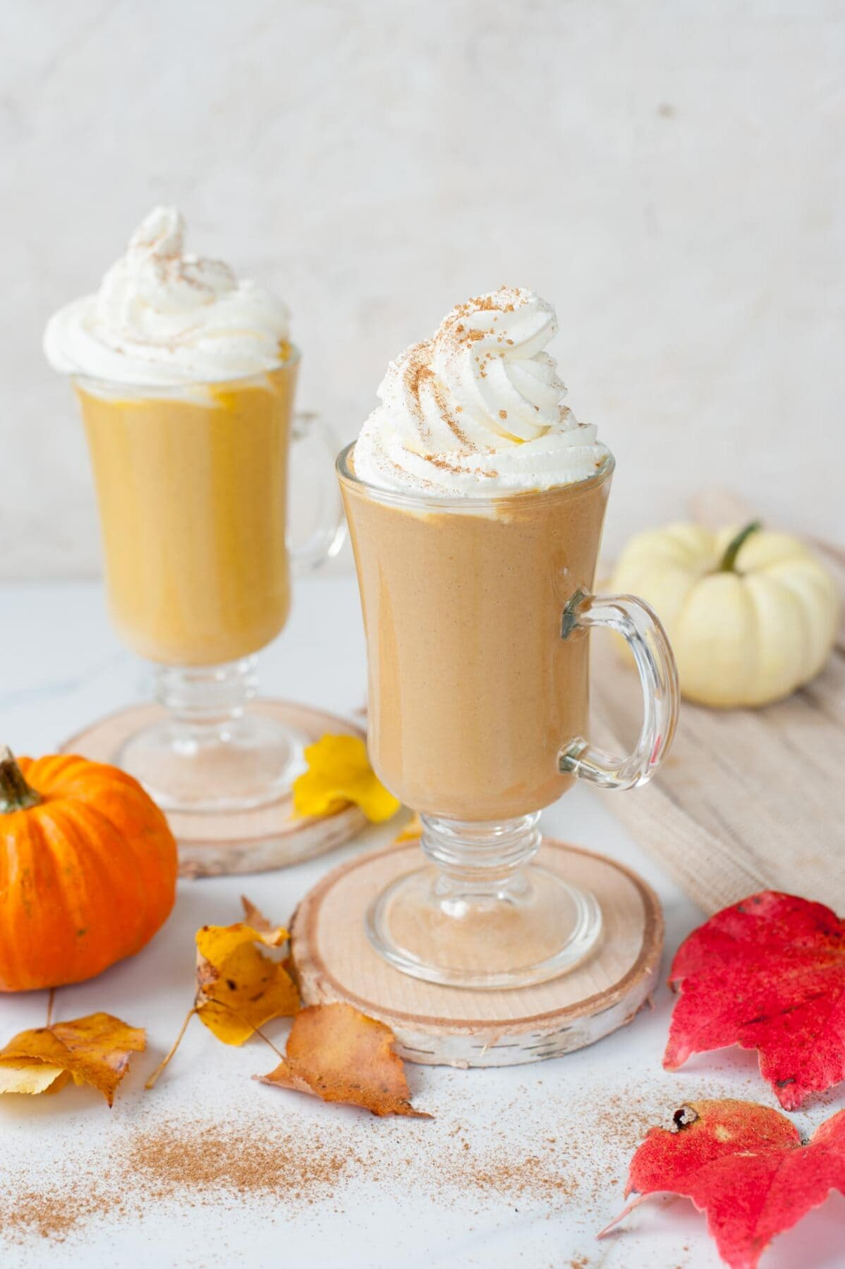 Two glasses with pumpkin hot chocolate topped with whipped cream. Small pumpkin and leaves scattered around.