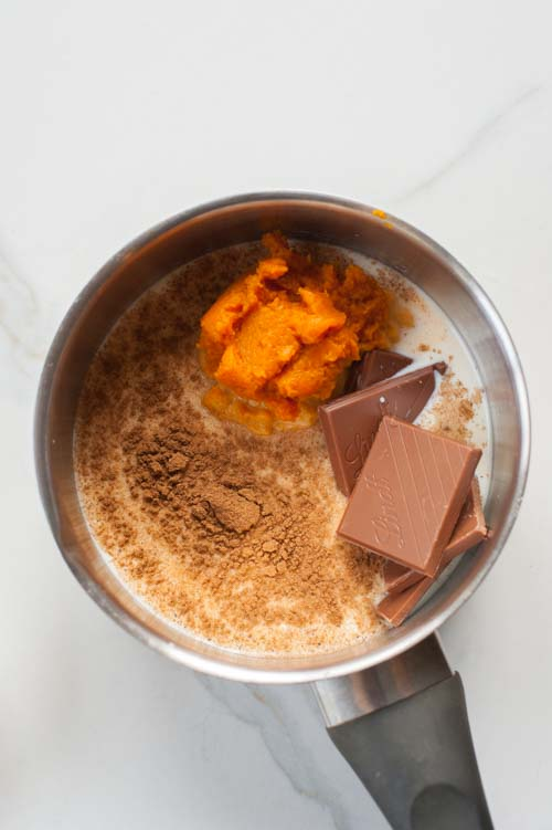 Ingredients for pumpkin spice hot chocolate in a small pot.