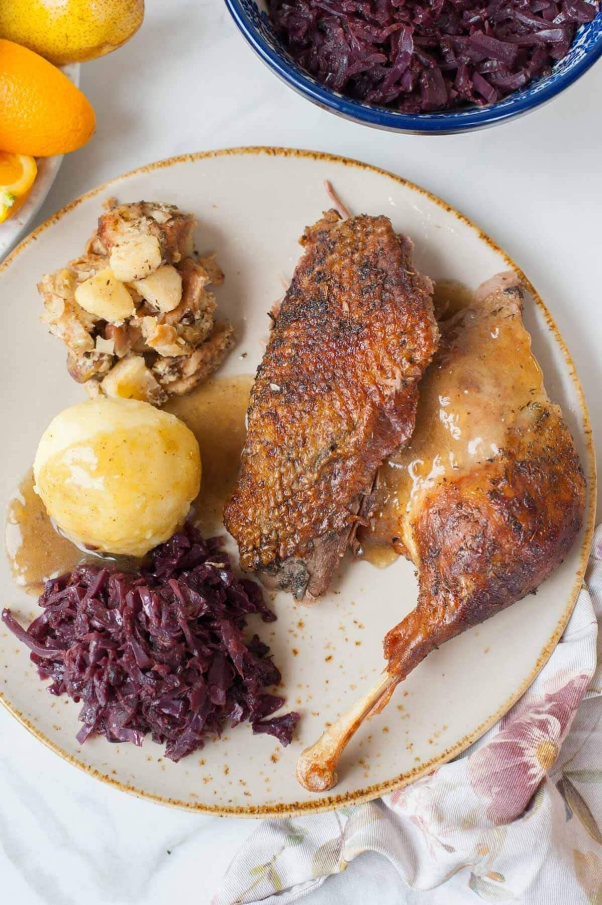 Goose breast and leg on a brown plate with stuffing, potato dumpling, braised red cabbage, and gravy.