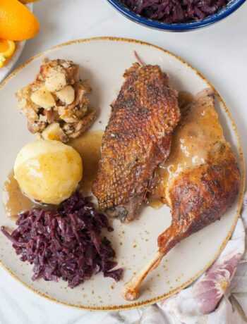 Roast goose leg and breast on a brown plate with braised cabbage and potato dumplings.
