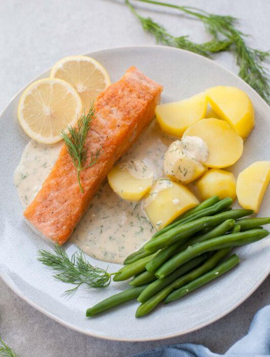 Salmon with creamy dill sauce, potatoes, and green beans on a blue plate.