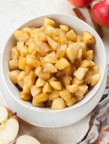 Sauteed cinnamon apples in a white bowl.
