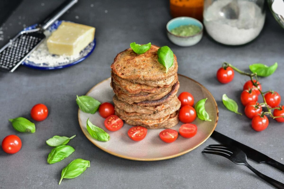 A stack of buckwheat pancakes on a brown plate with basil leaves and cherry tomatoes.