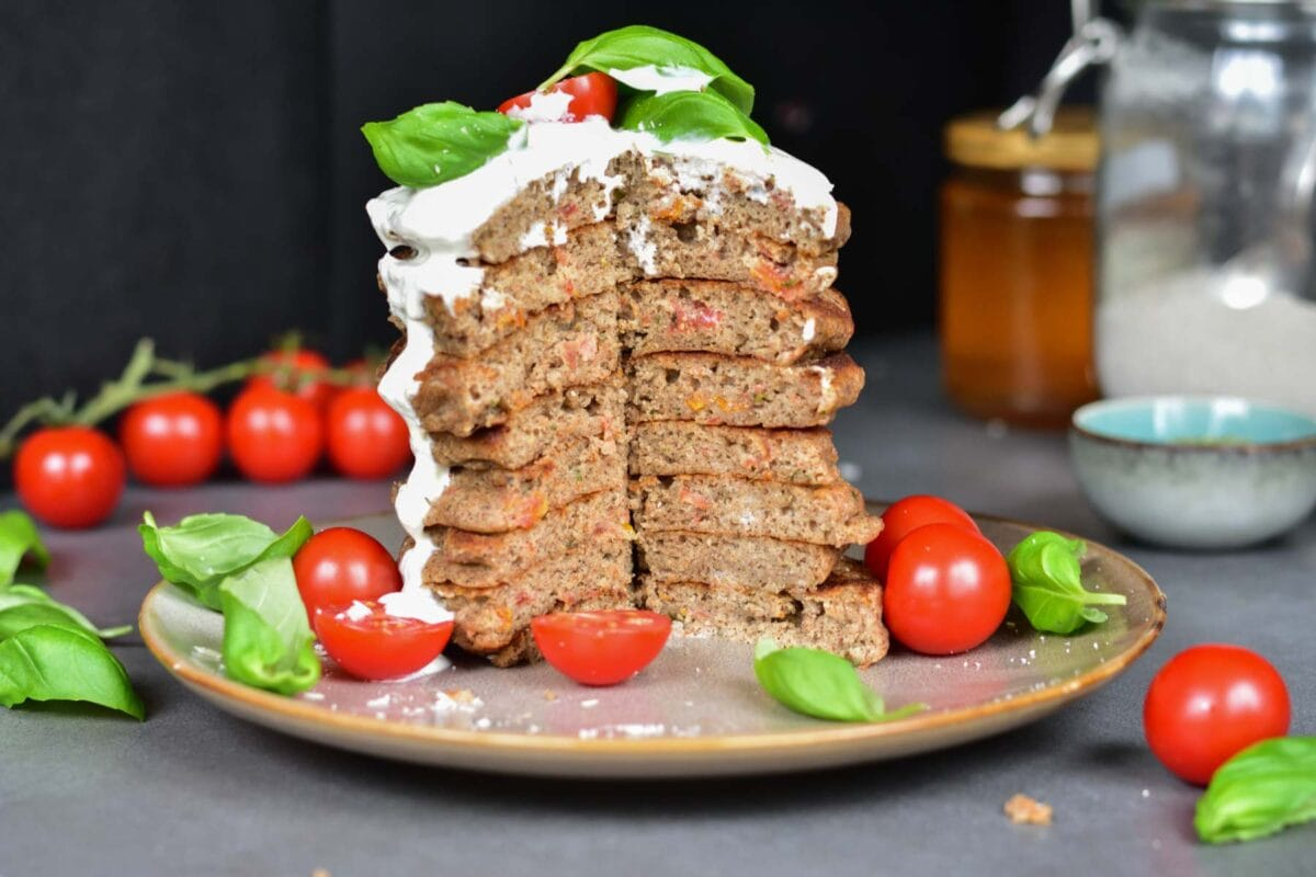 A stack of buckwheat pancakes with a quarter missing on a brown plate served with yogurt, basil leaves, and cherry tomatoes.