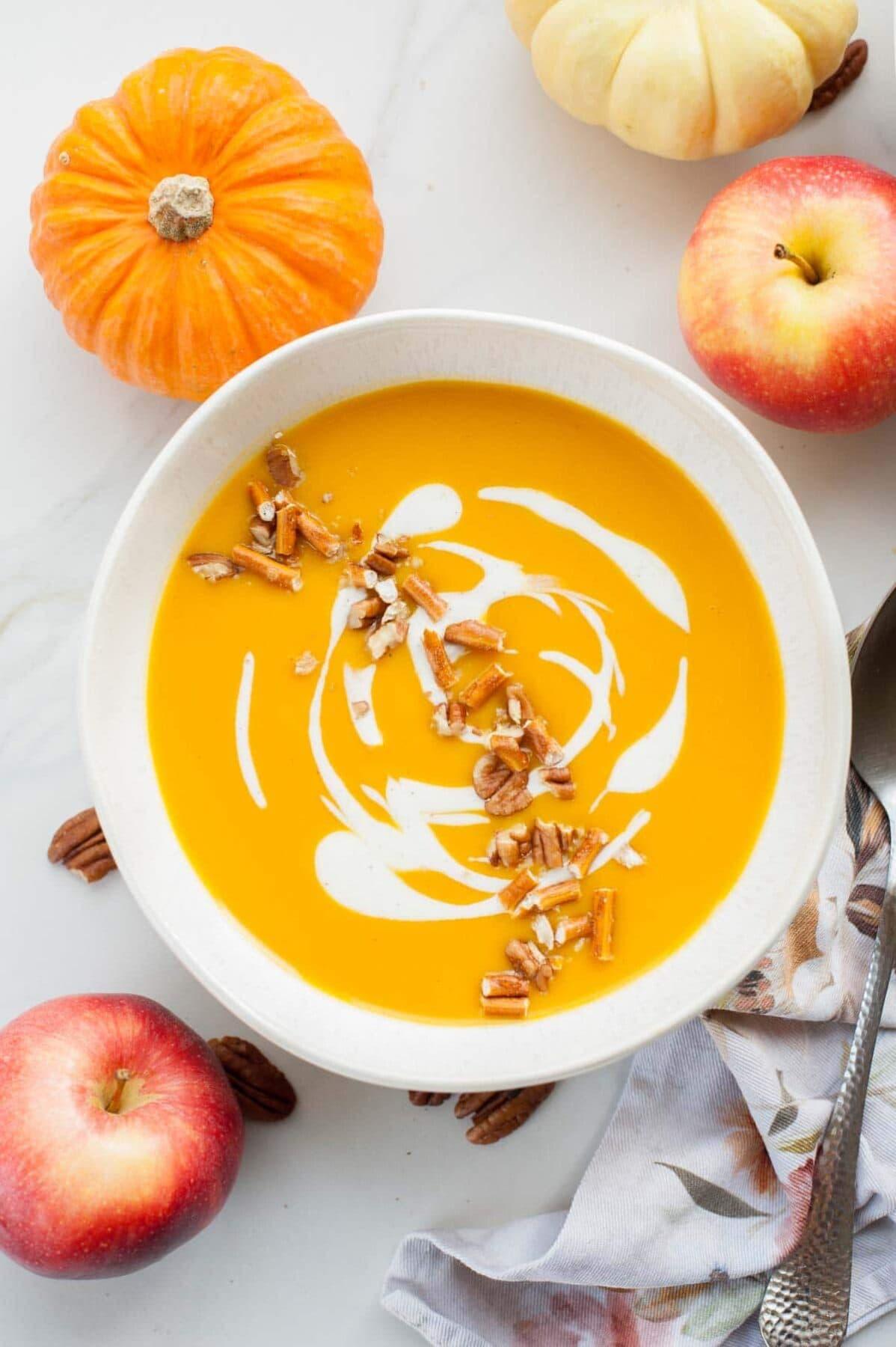 Biała miska z zupą dyniową z jabłkiem. Jabłka i łyżka w tle.