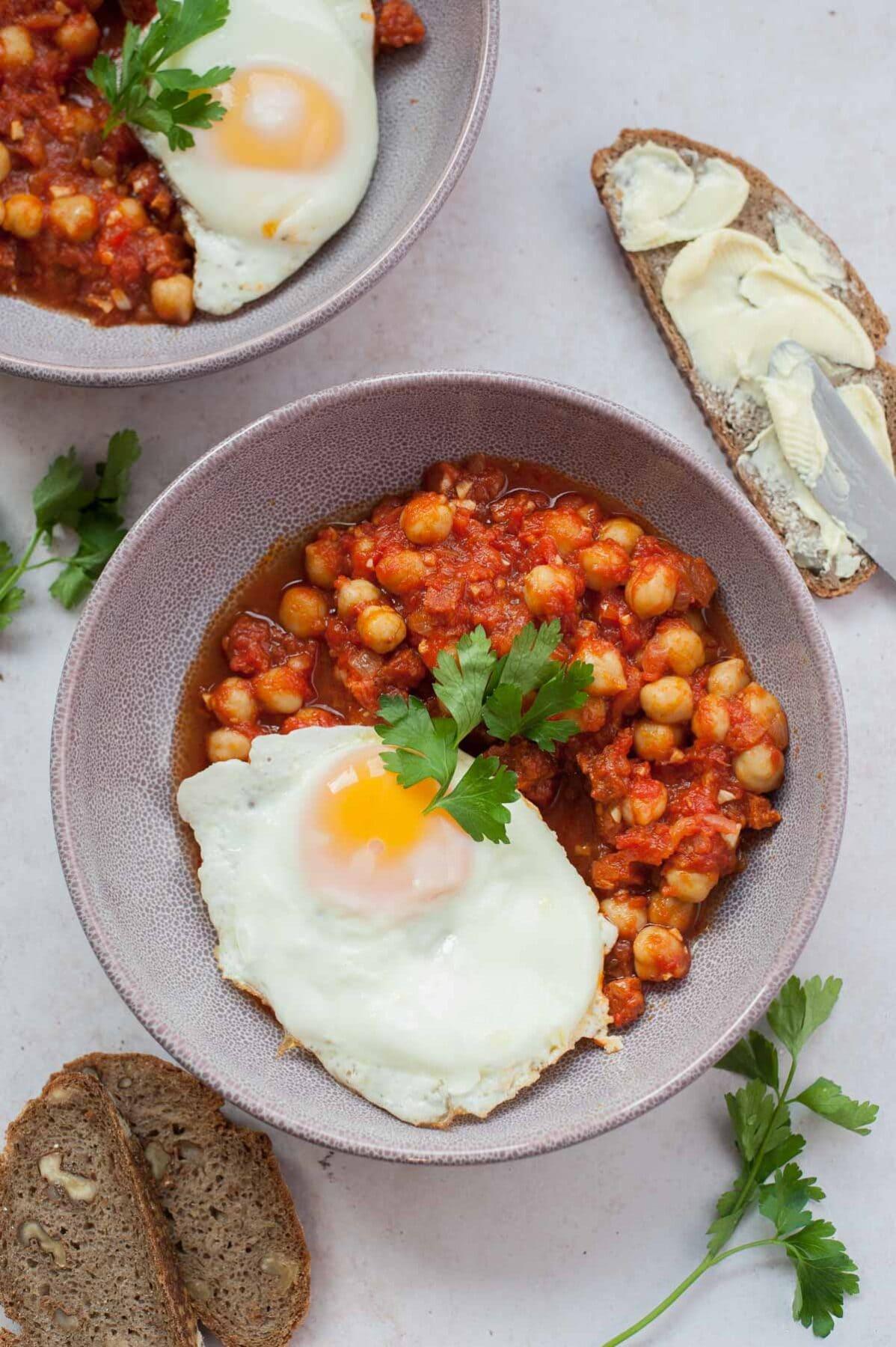 Ciecierzyca z chorizo w sosie pomidorowym z jajkiem sadzonym i pietruszką w fioletowym talerzu.
