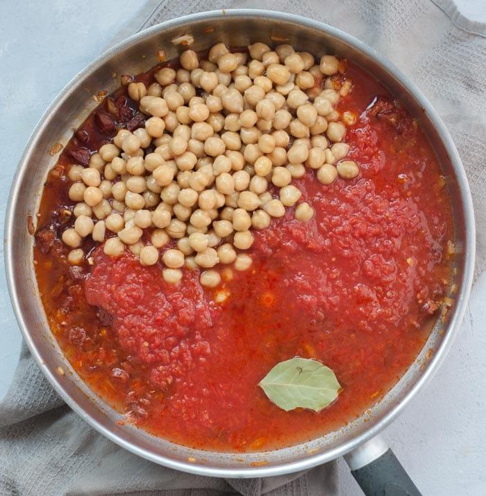 Kiełbasa chorizo z cebulą, sosem pomidorowym i ciecierzycą na patelni.
