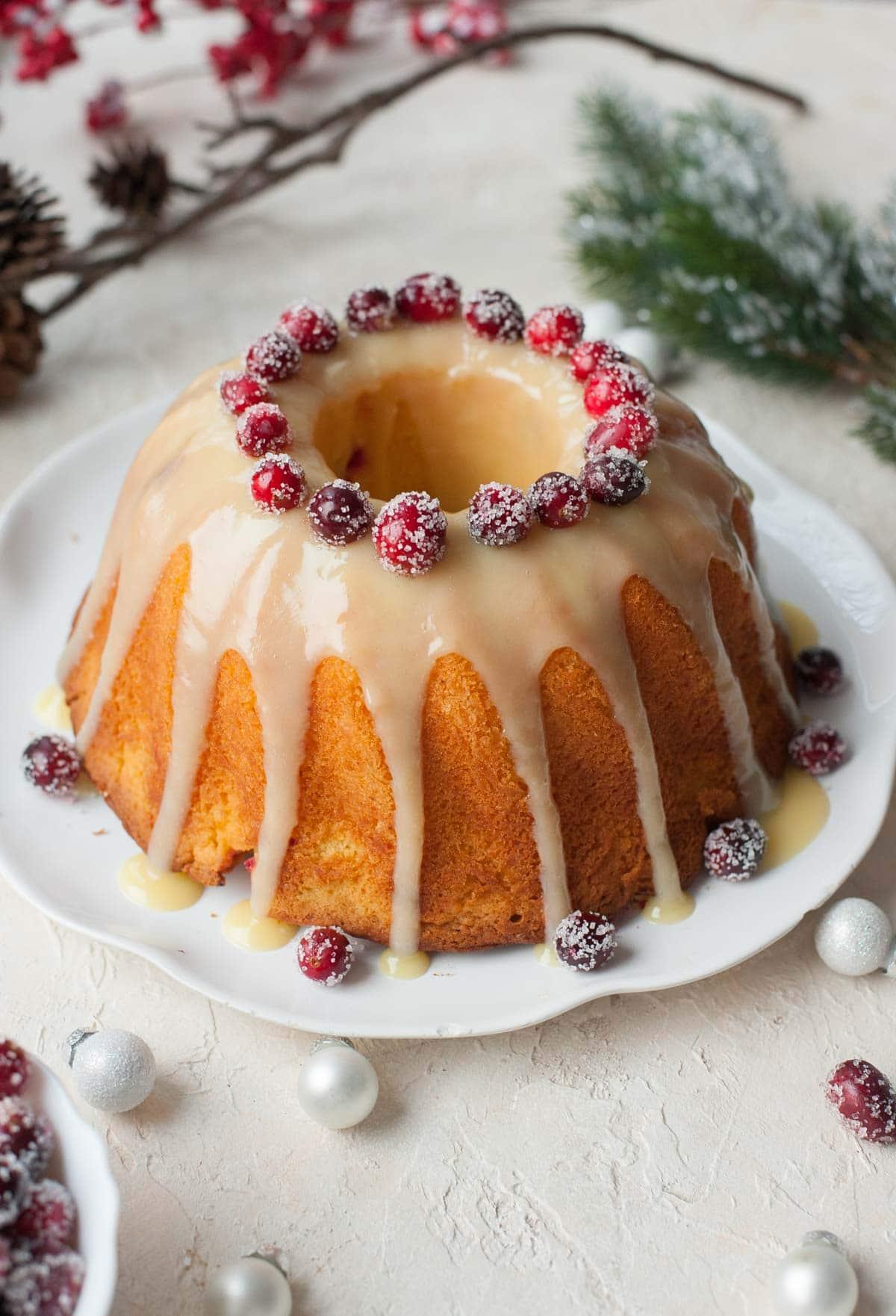 Cranberry orange bundt cake with white chocolate orange glaze and sugared cranberries.