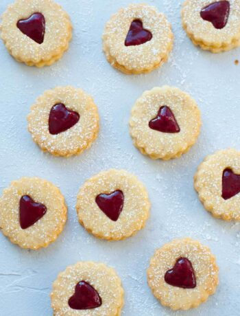Raspberry Linzer cookies on a blue background.