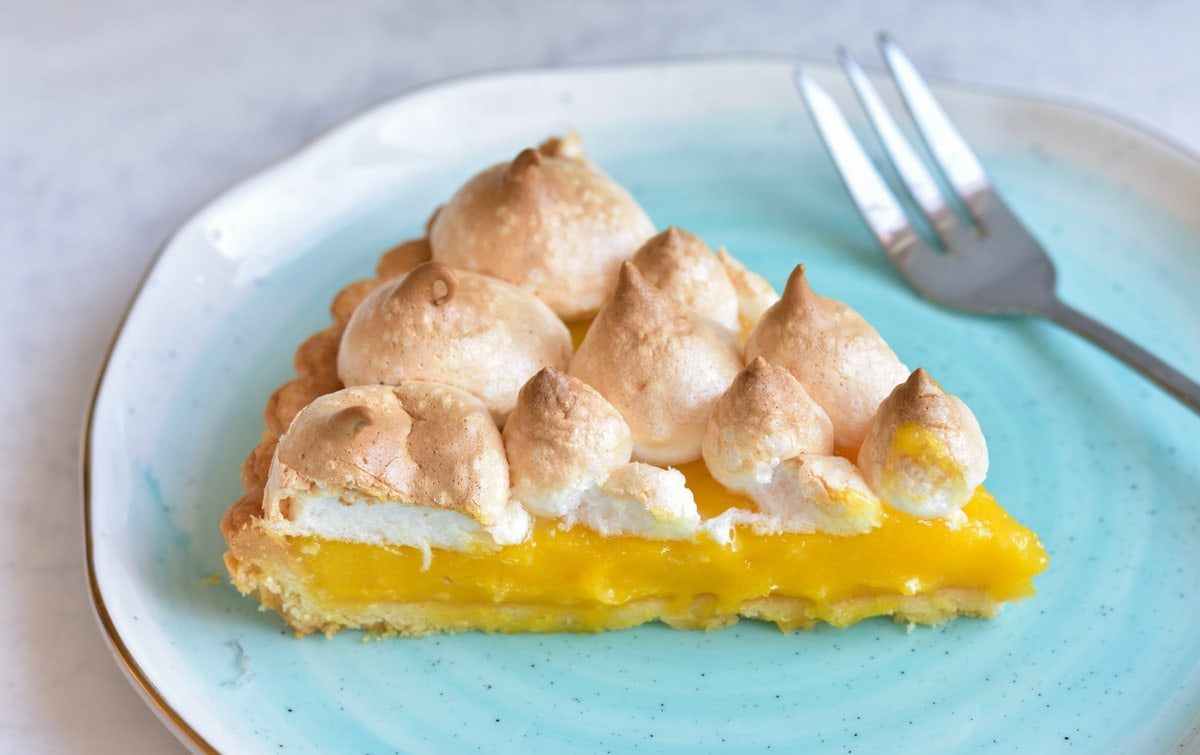 A piece of passion fruit tart on a blue plate.