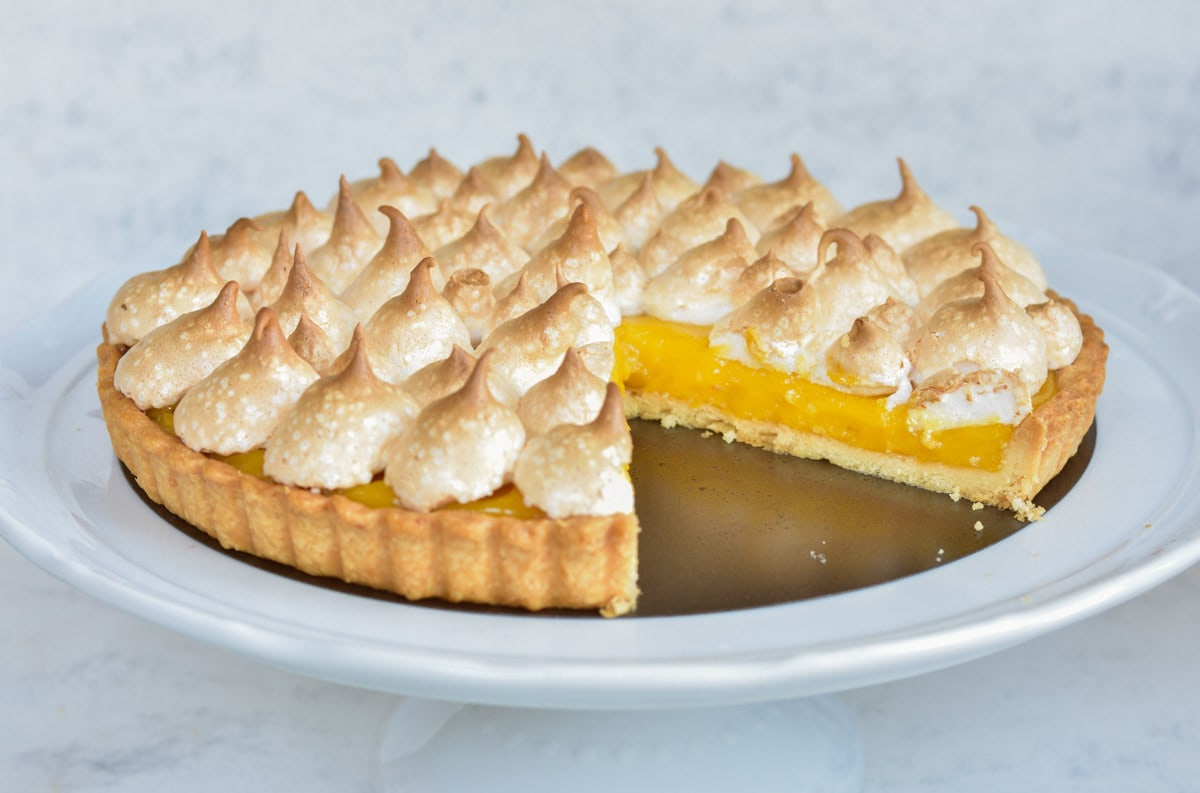 Passion fruit tart on a white cake stand.