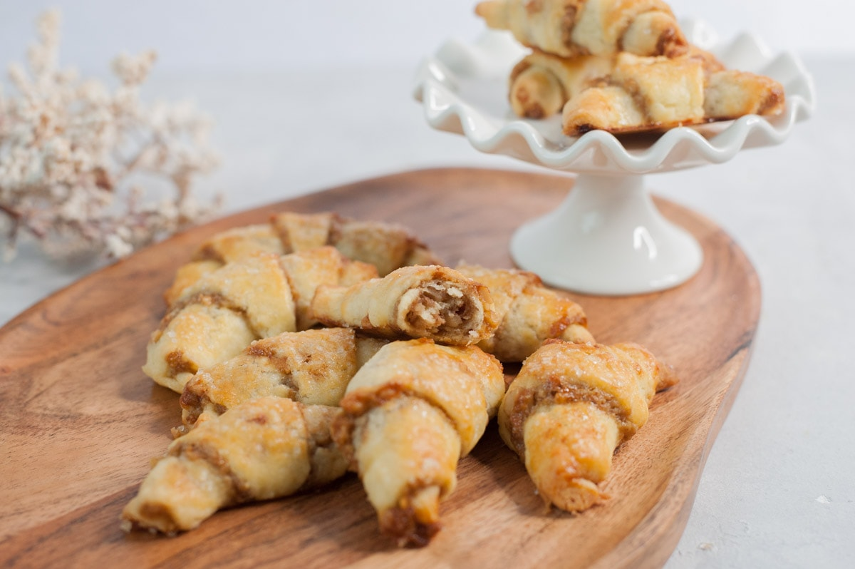 Orange walnut rugelach on a chopping board. White cake stand and white plants in the background.