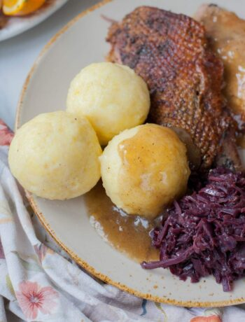 Potato dumplings on a brown plate with braised cabbage and roast goose.
