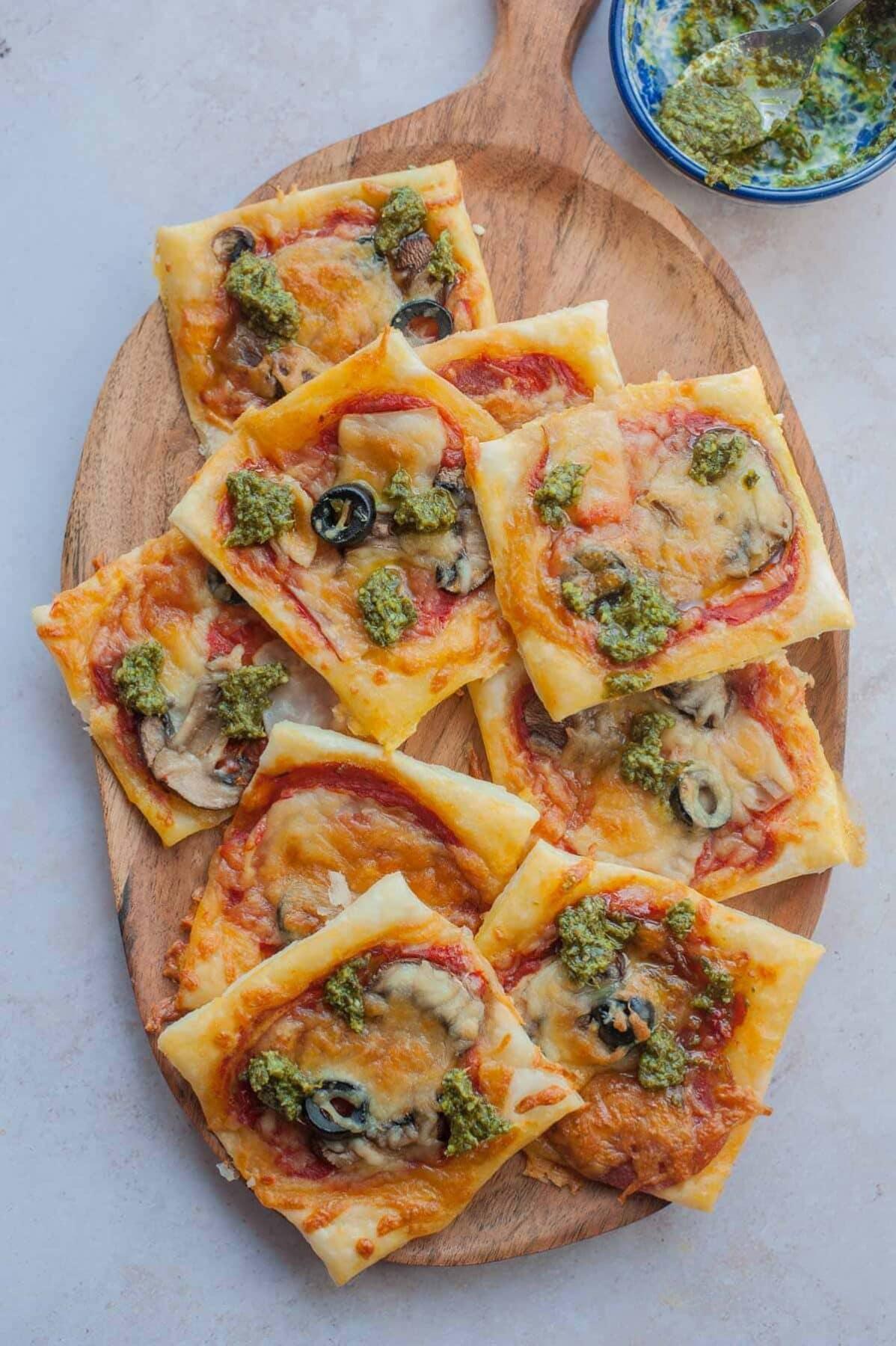 Mini pizze z ciasta francuskiego na drewnianej desce.