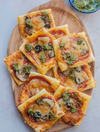 Puff pastry pizza bites on a wooden serving tray.