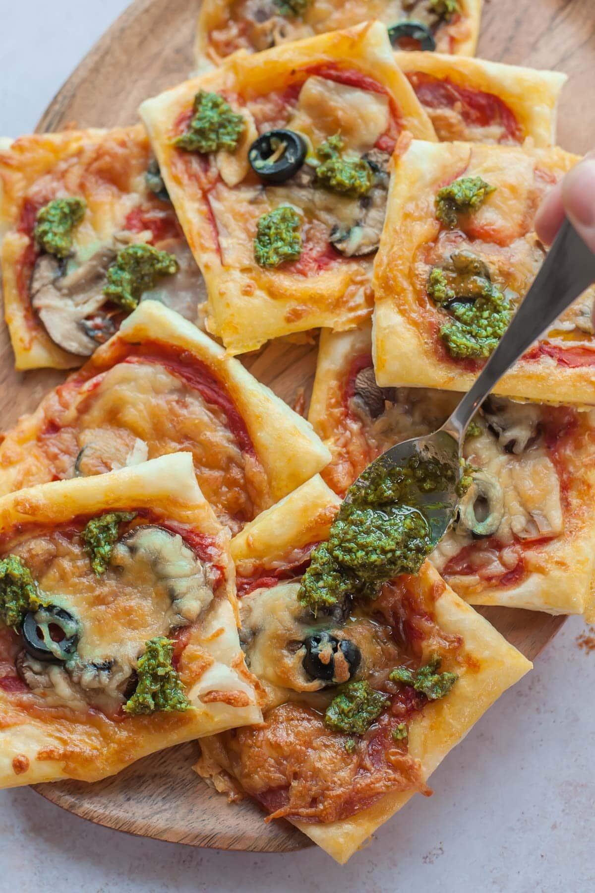 Mini pizze z ciadta francuskiego polewane sosem pesto.