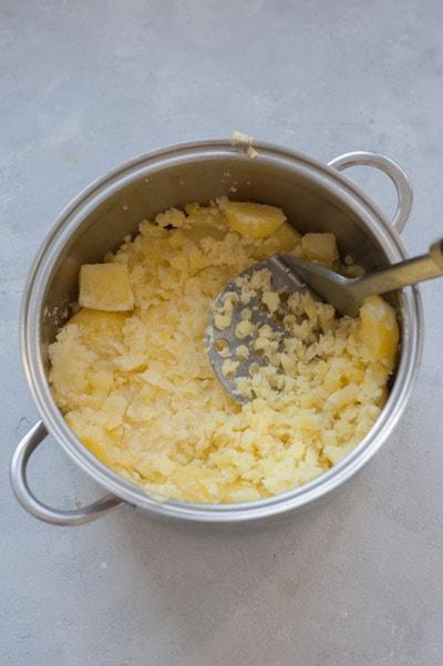 Ziemniaki miażdżone tłuczkiem do ziemniaków w garnku.