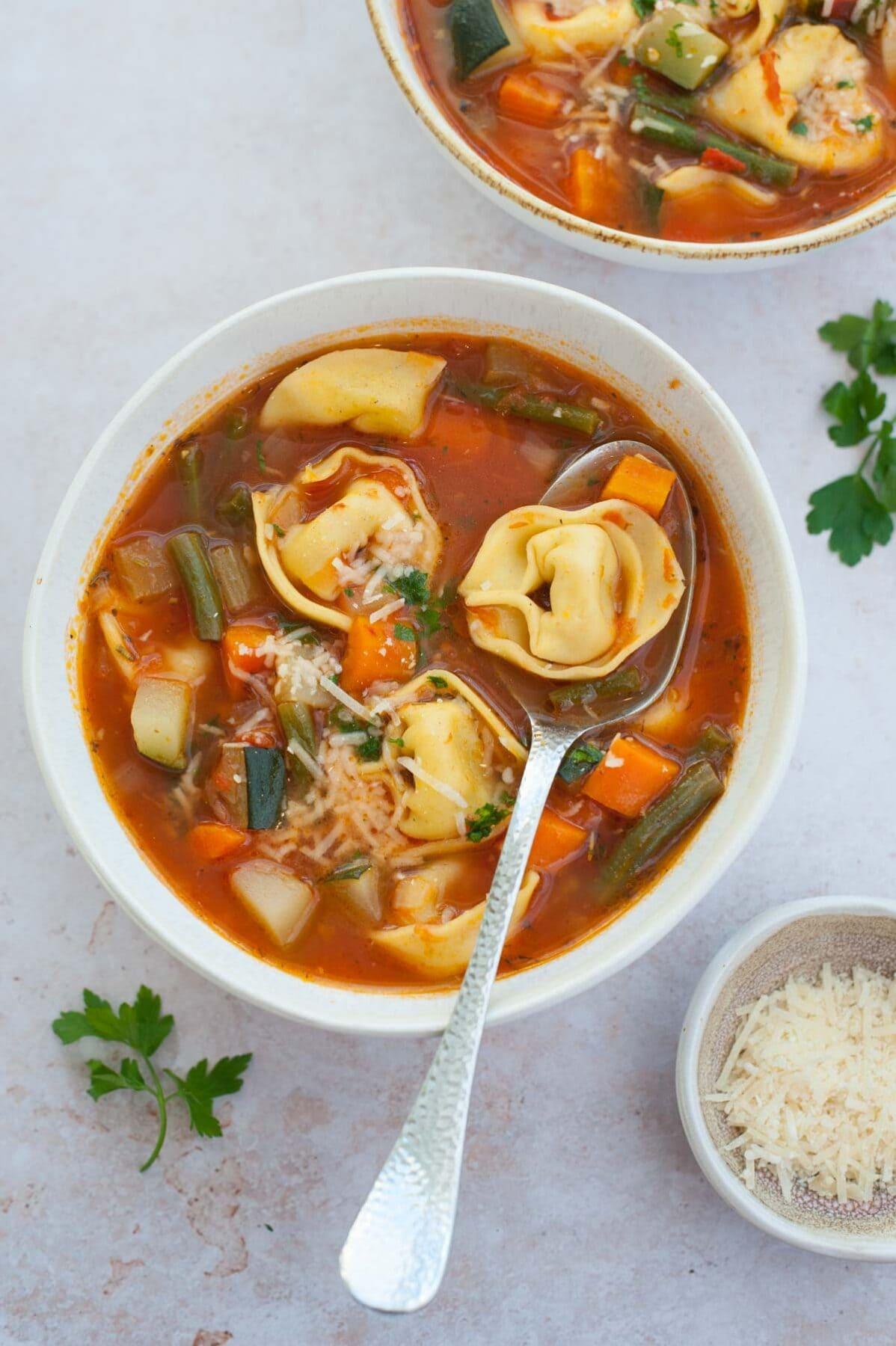 Dwie białe miski z zupą warzywną z tortellini.