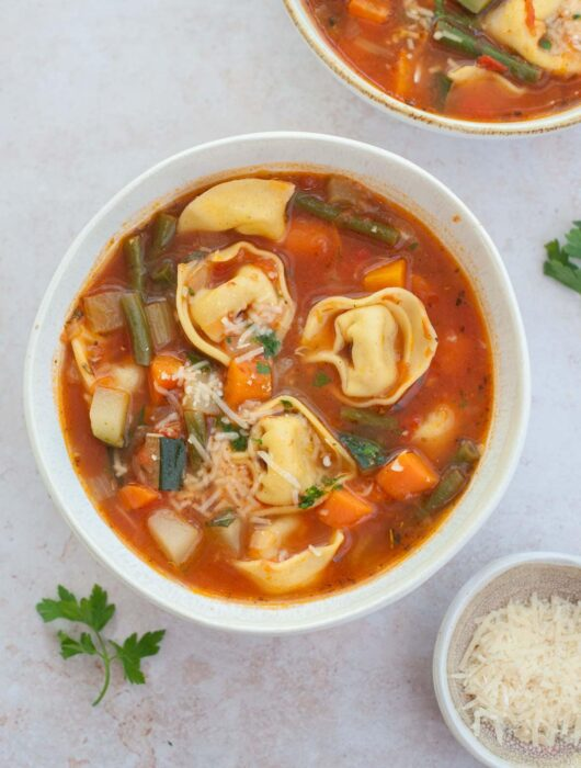 Two white bowls with vegetable tortellini soup.