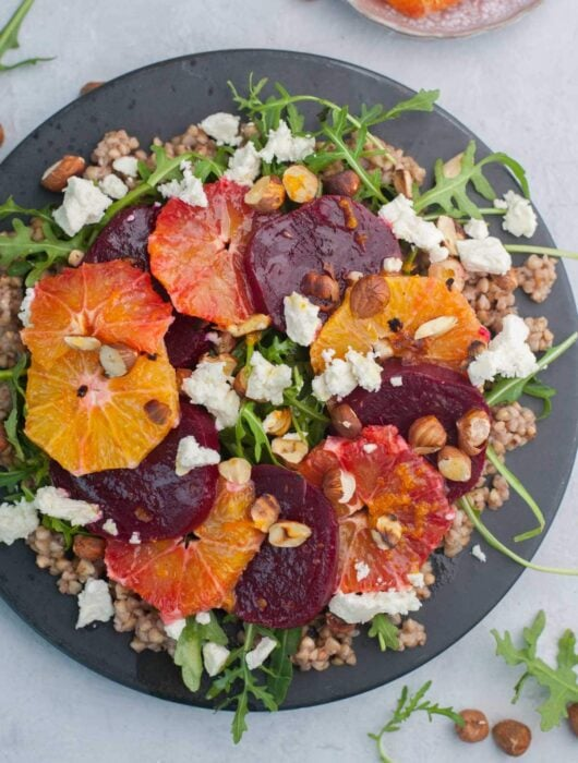 Buckwheat salad with beets, oranges, arugula, and feta cheese on a black plate.