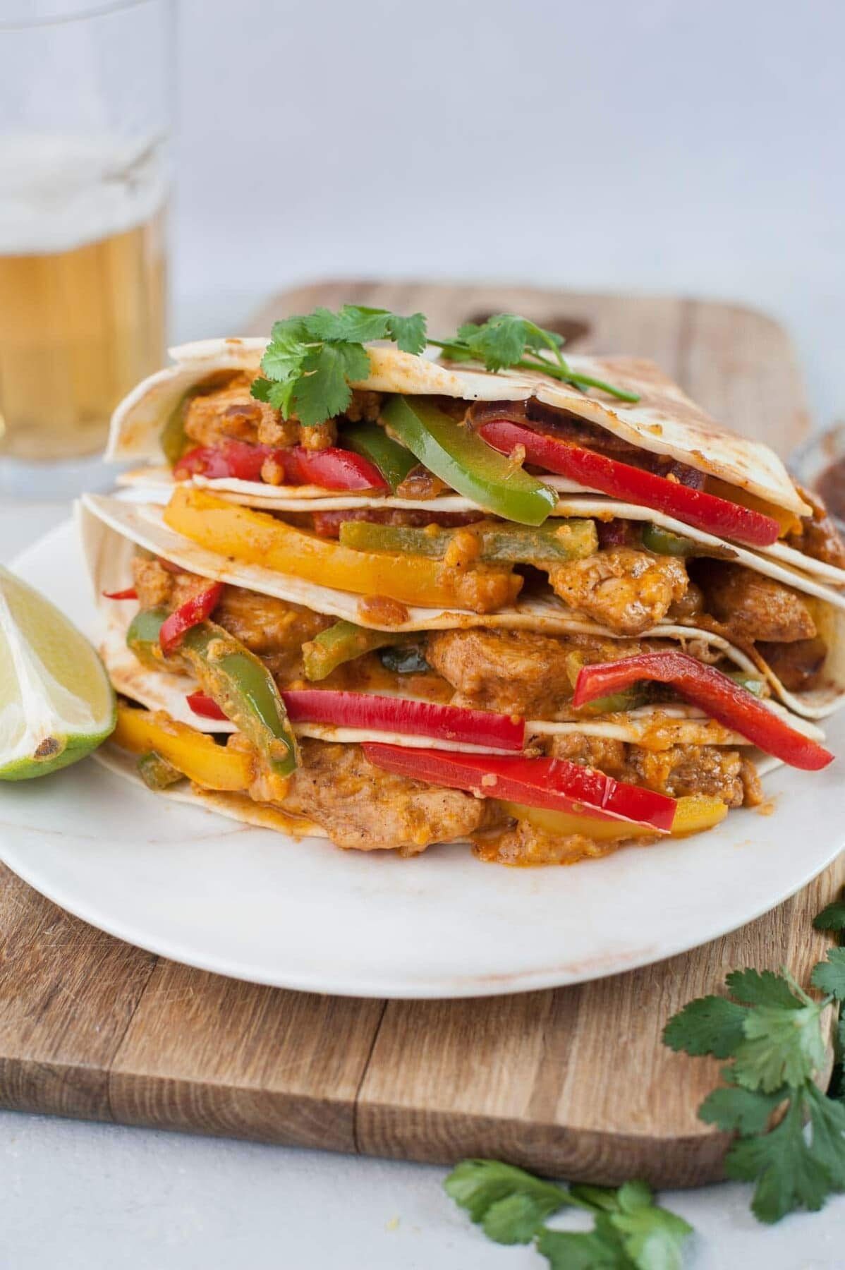 Chicken fajita quesadillas on a wooden boards topped with cilantro leaves.