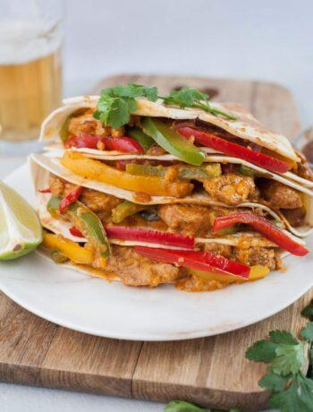 Chicken fajita quesadillas on a wooden boards topped with cilantro leaves.
