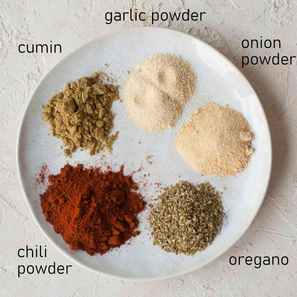 Labeled spices on a white plate needed to make fajita seasoning mix.