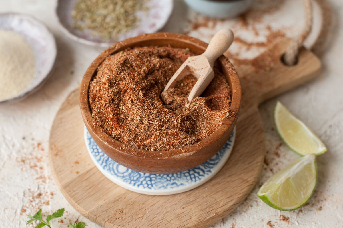 Fajita seasoning in a brown bowl. Limes and spices in the background.