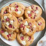 Fresh cranberry white chocolate cookies on a silver tray.