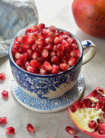 Pomegranate seeds in a blue cup.