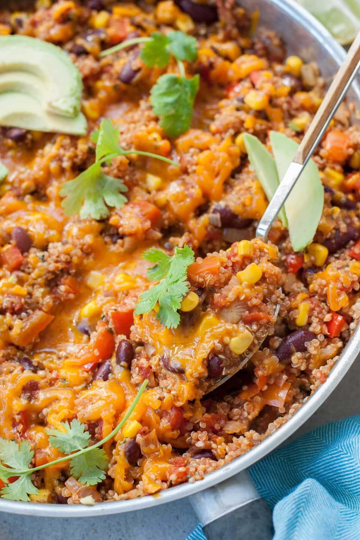 Quinoa po meksykańsku nabierana łyżką z patelni do smażenia.