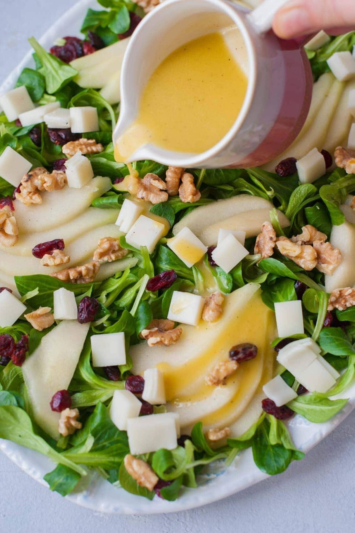 Sałatka z gruszką, żurawiną, orzechami włoskimi i kozim serem polewana sosem.