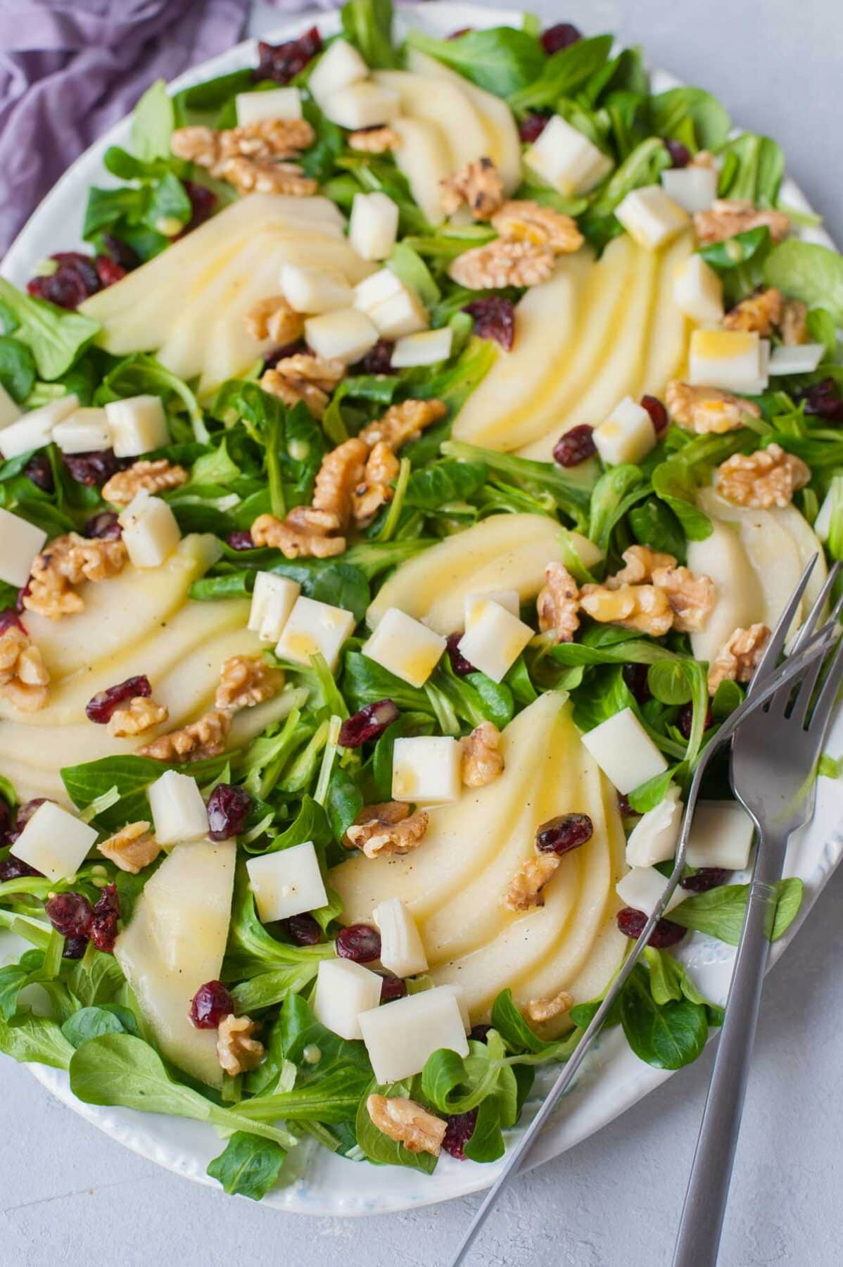 Pear walnut salad with cranberries and goat cheese on a white plate.