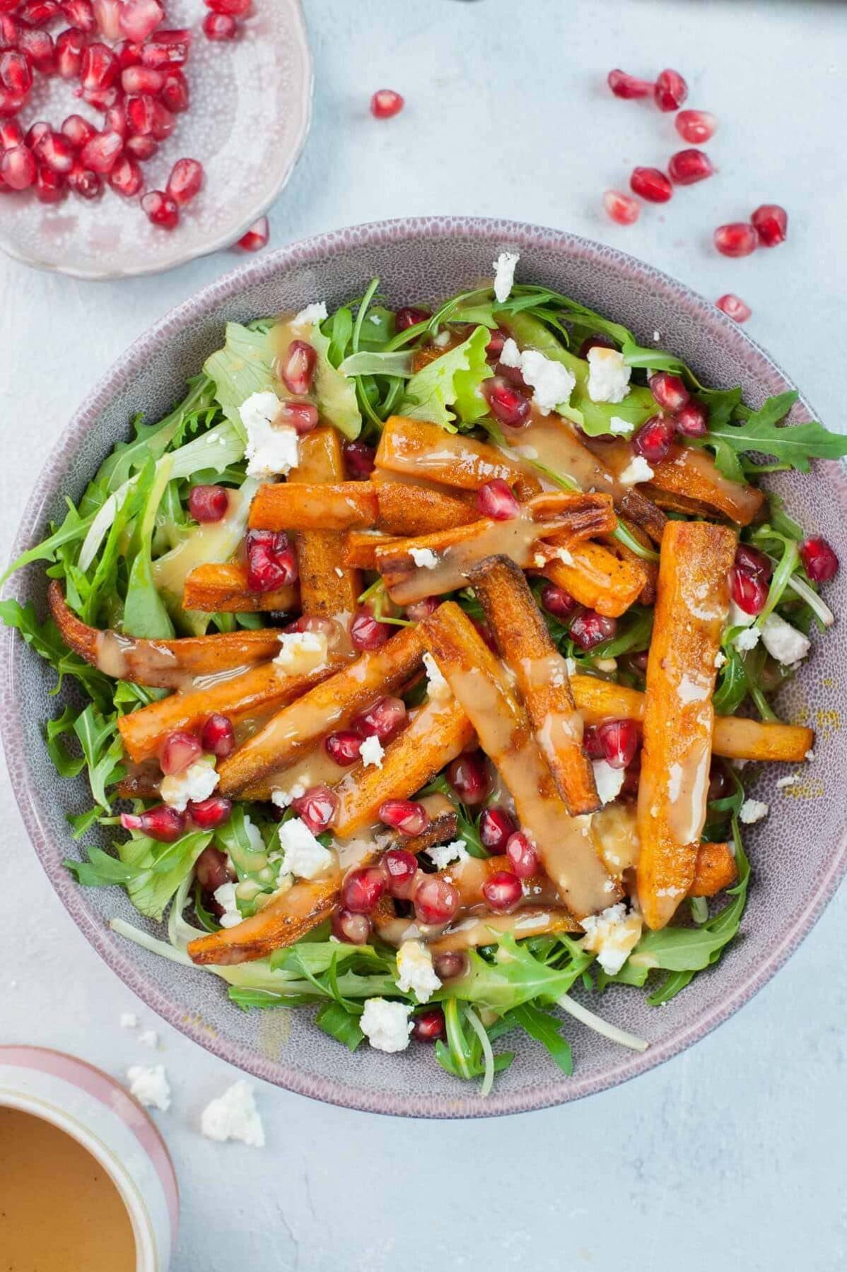 Roasted carrot salad with pomegranate and peanut butter lemon dressing in a violet bowl.