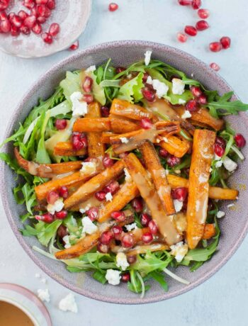 Roasted carrot salad with pomegranate, feta, and peanut butter lemon dressing in a violet bowl.