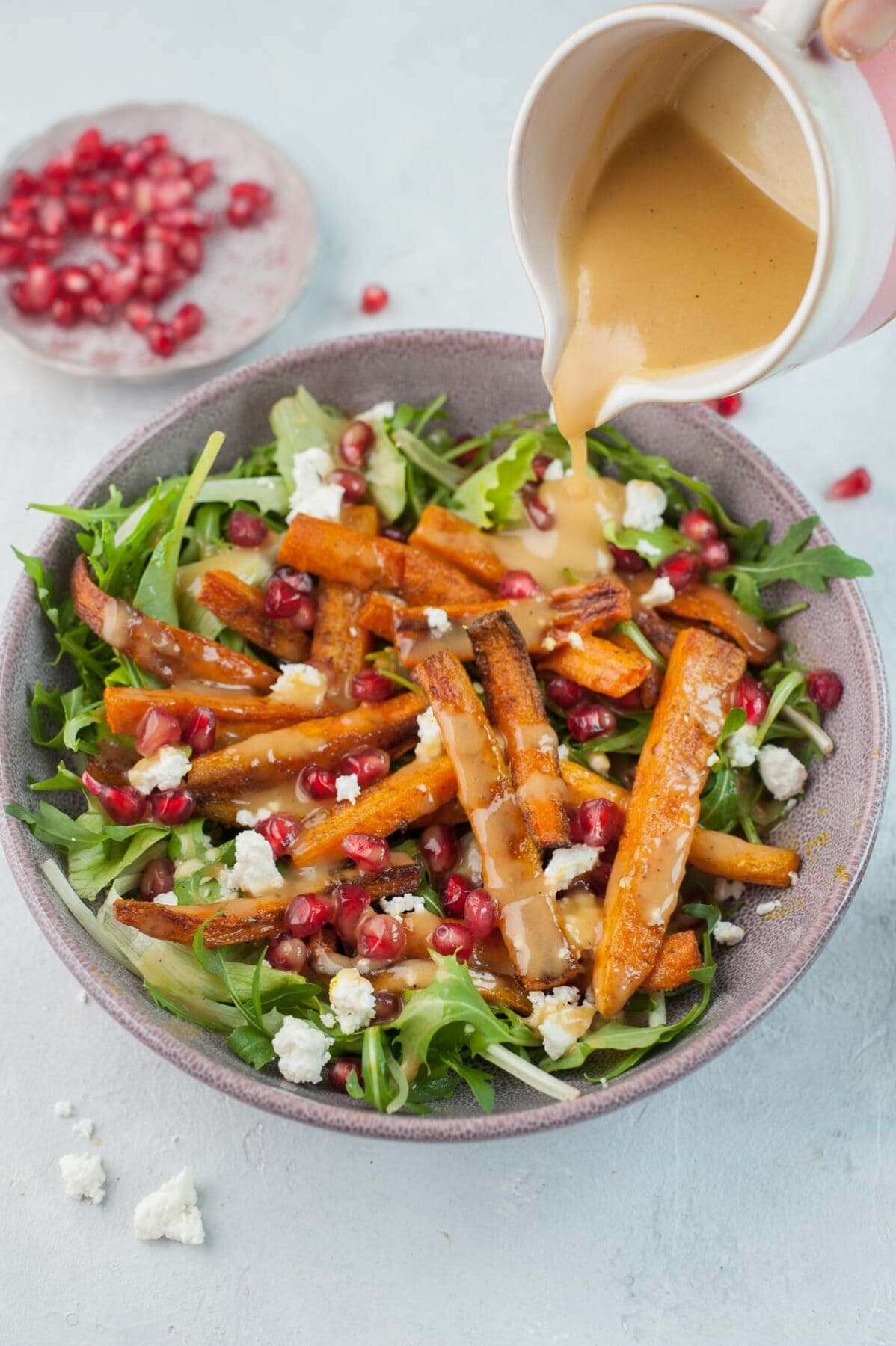 Peanut butter lemon dressing is being poured over roasted carrot salad.