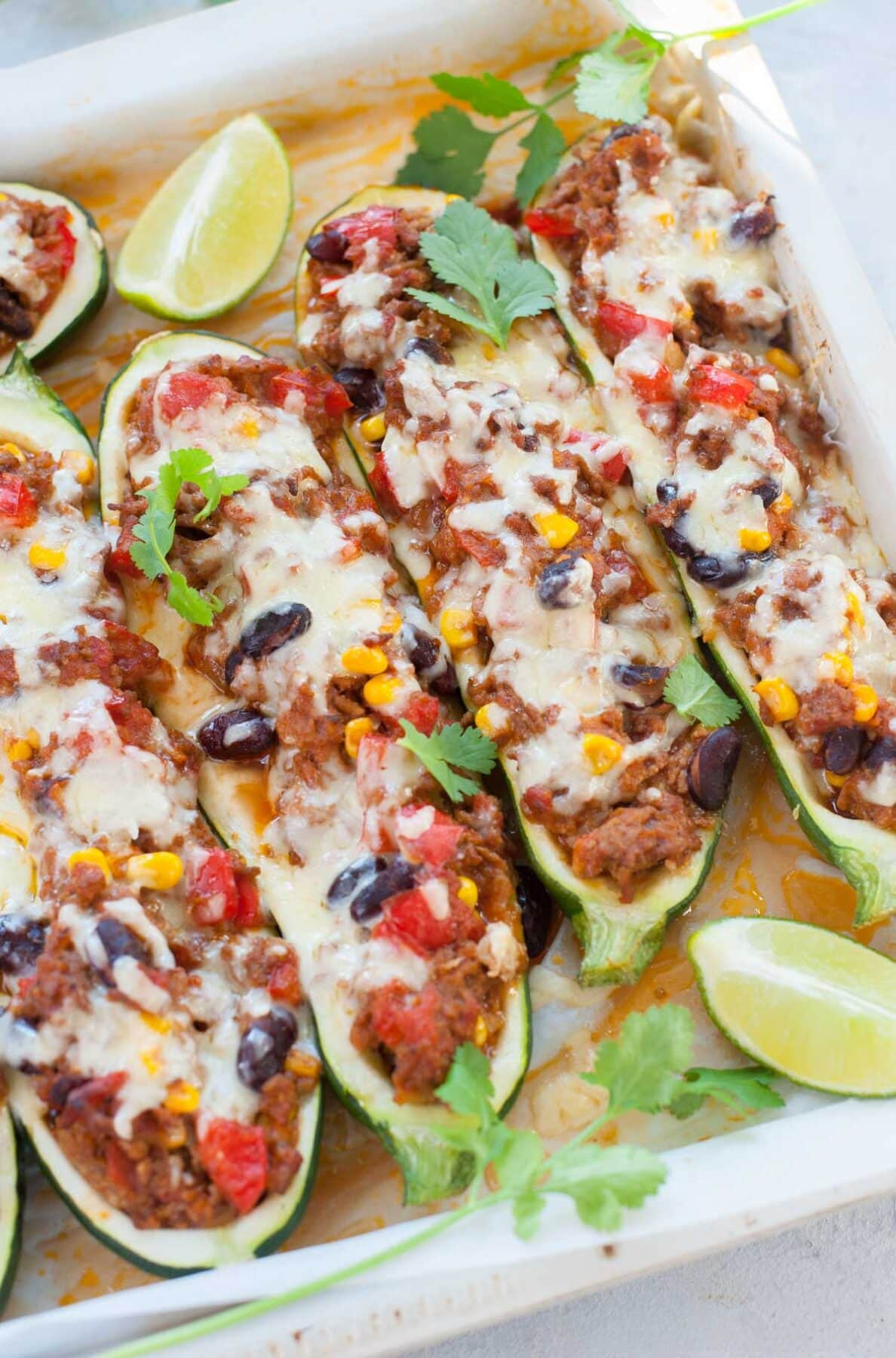 Mexican zucchini boats in a white baking pan topped with cilantro.