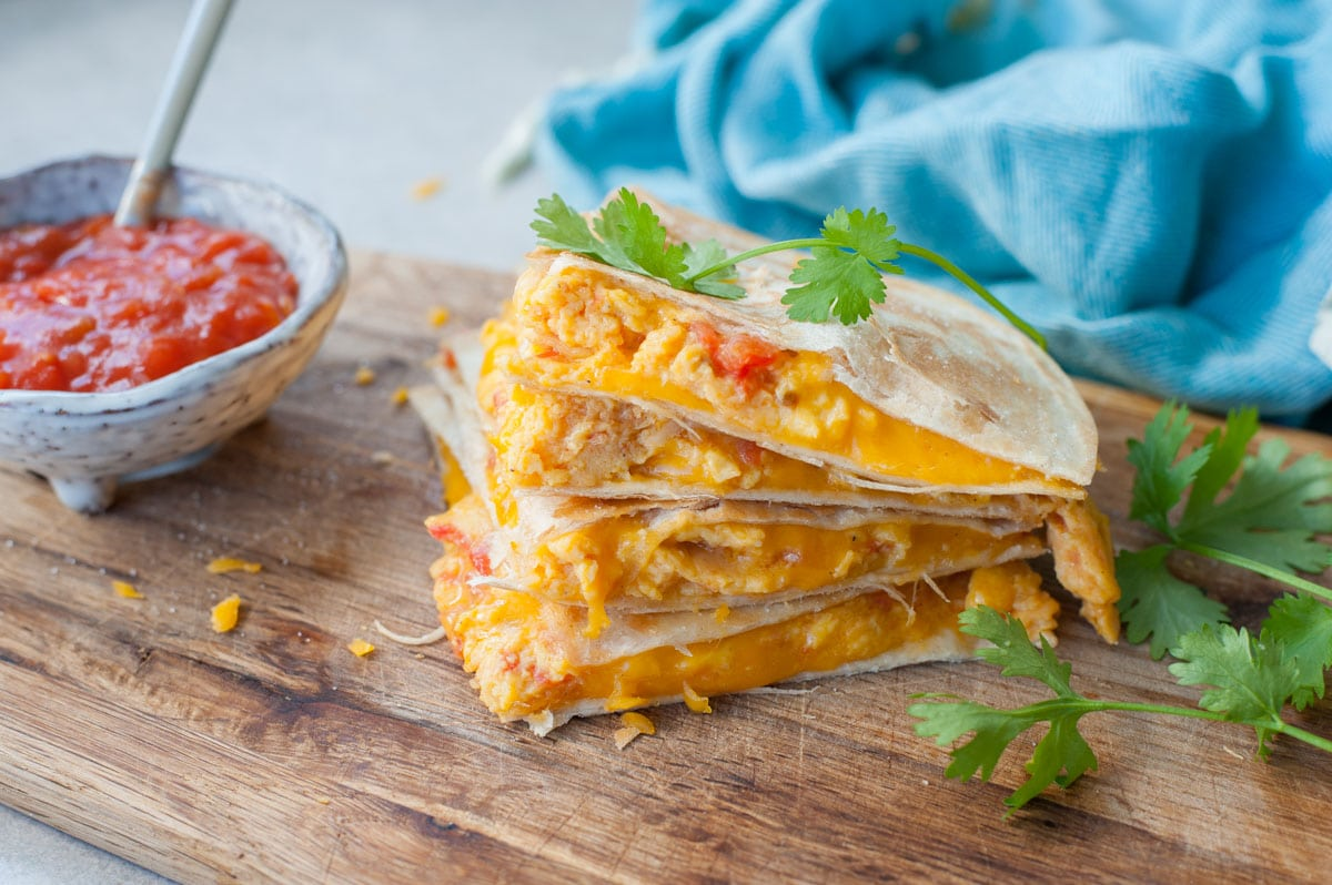 A stack of breakfast quesadillas on a wooden board. Tomato salsa and cilantro in the background.