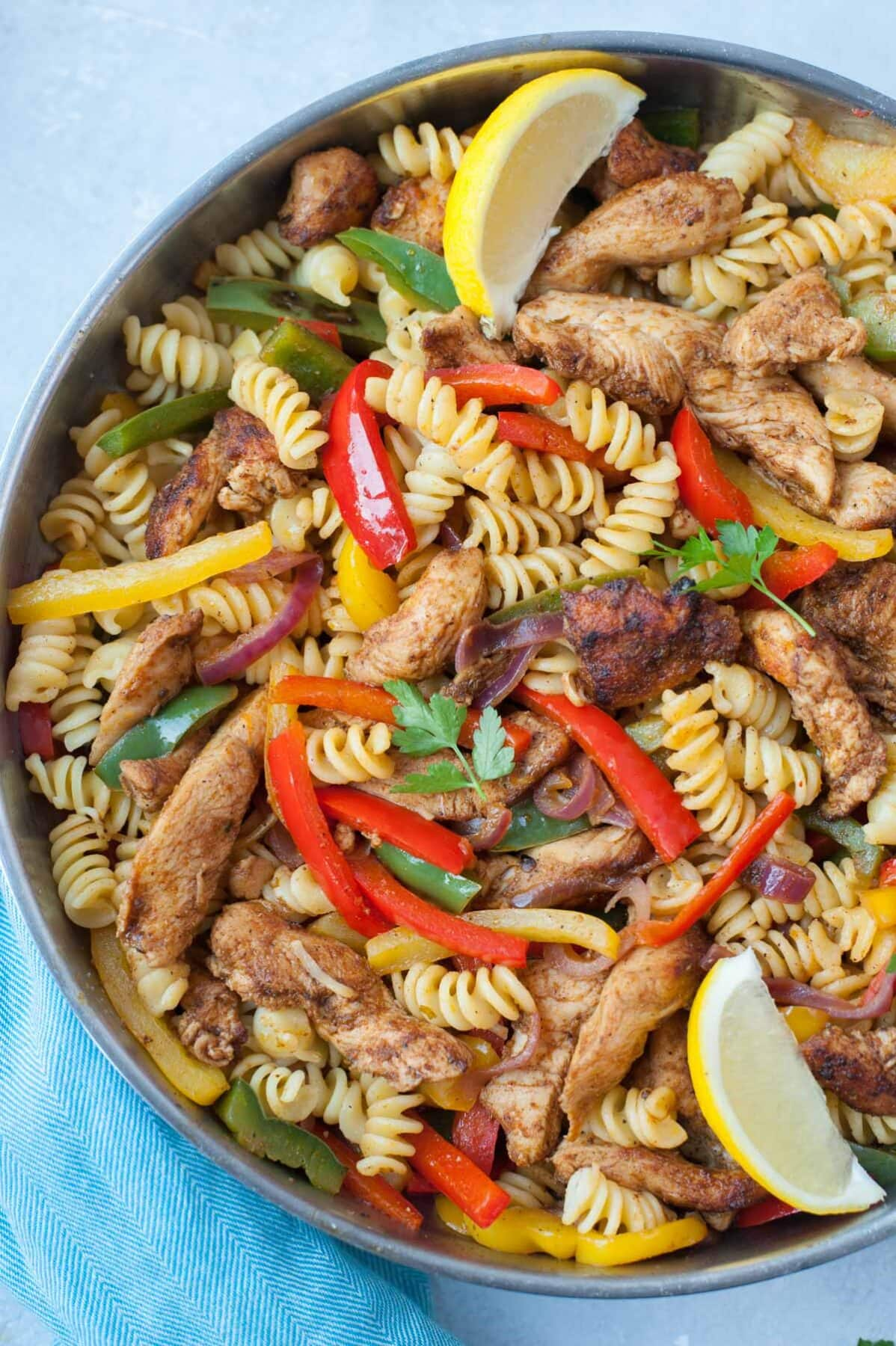 A close up picture of chicken fajita pasta in a frying pan.