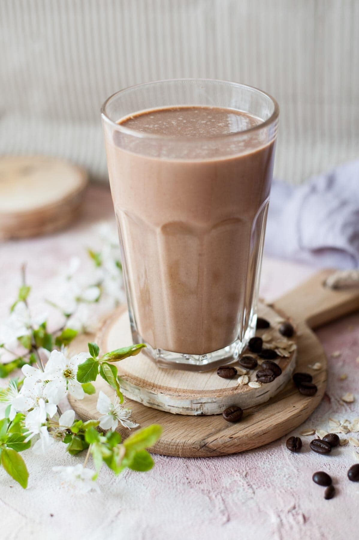 Coffee banana smoothie in a glas. Branch with flowers and coffee beans in the background.