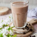 Coffee banana smoothie in a glass. Flowers and coffee beans on the side.