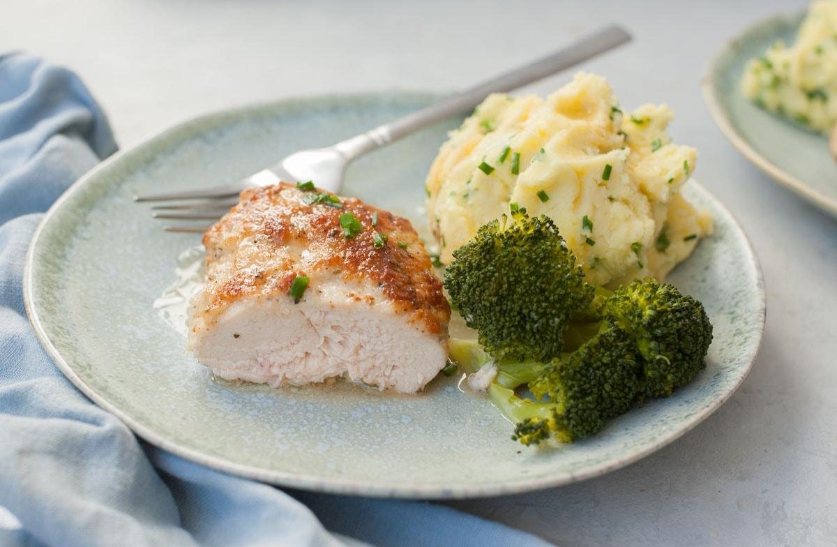 Piersi z kurczaka przekrojone na pół w majonezie na zielonym talerzu z ziemniakami i brokułami.