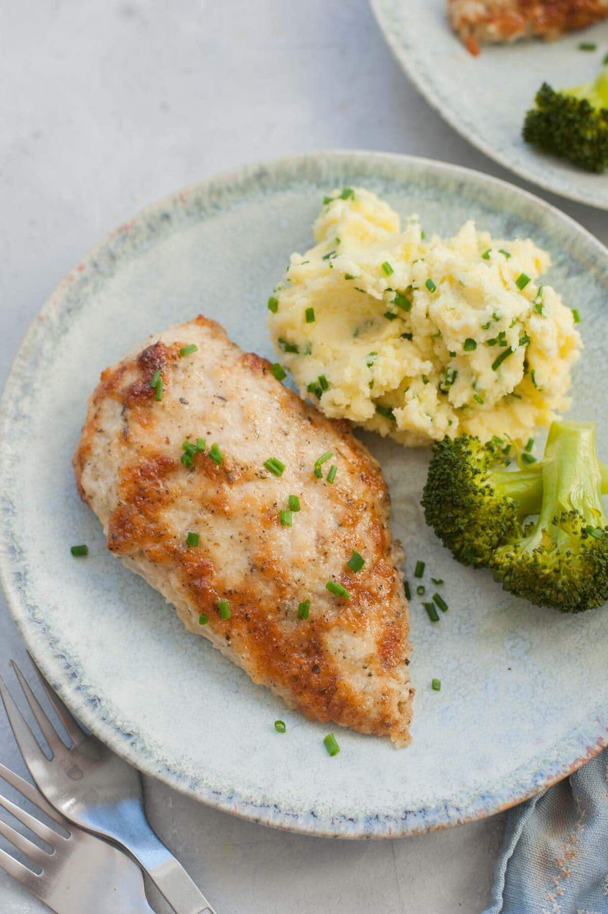 Piersi z kurczaka w majonezie na zielonym talerzu z ziemniakami i brokułami.