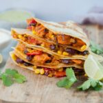 Vegetarian quesadillas on a wooden chopping board, surrounded with cilantro and lime quarters.