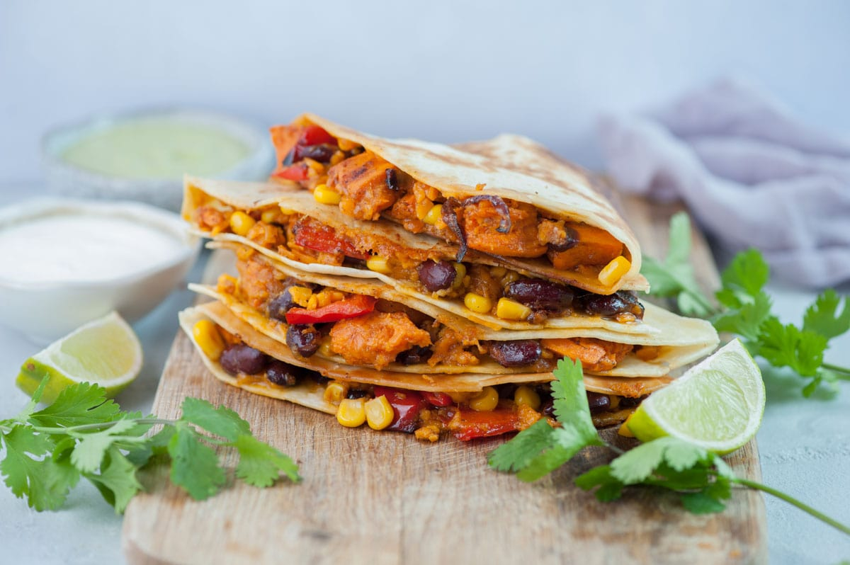 Sweet potato, beans, corn, and bell pepper quesadillas on a wooden chopping board, surrounded with cilantro leaves and limes.
