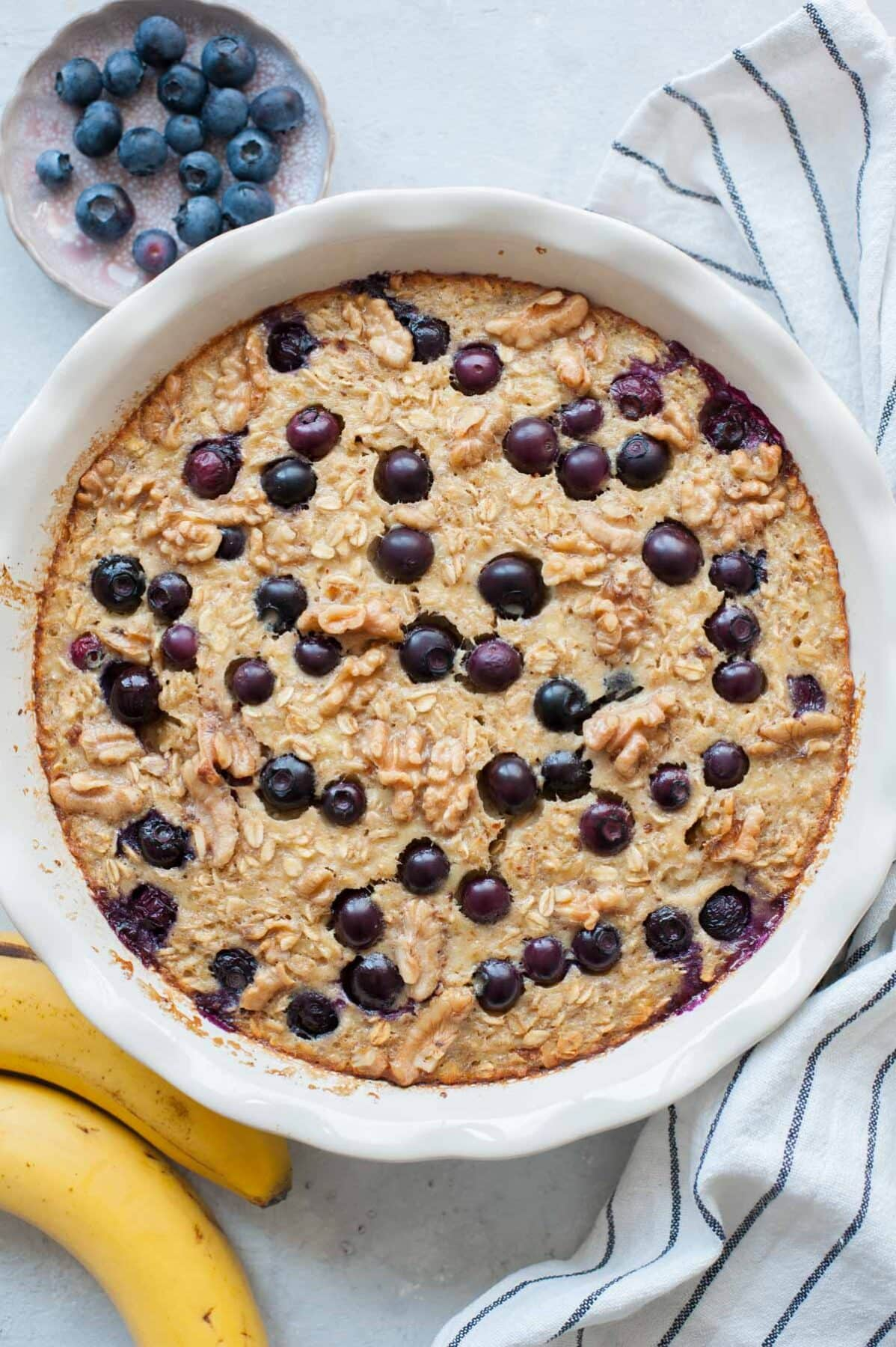 Baked oatmeal on a white table with striped towel near a banana and plate of blueberries
