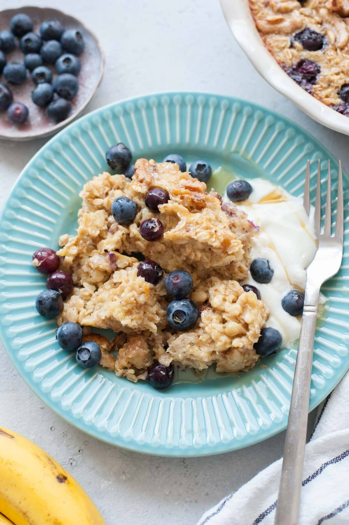 Baked oatmeal with blueberries and banana on a light blue plate, served with yogurt and maple syrup.