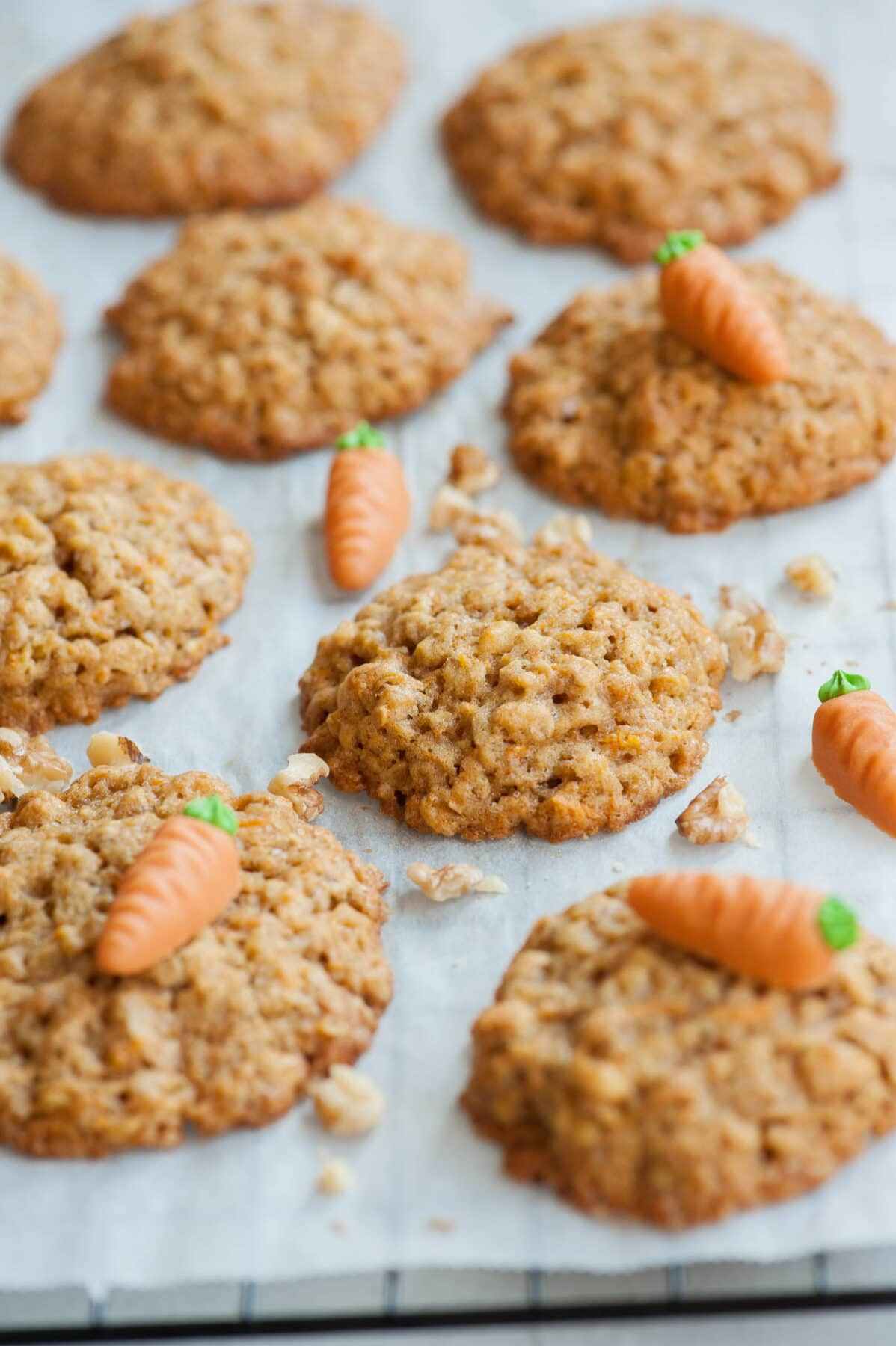 Carrot cake cookies on a piece of parchment paper, topped with marzipan carrots and walnuts.